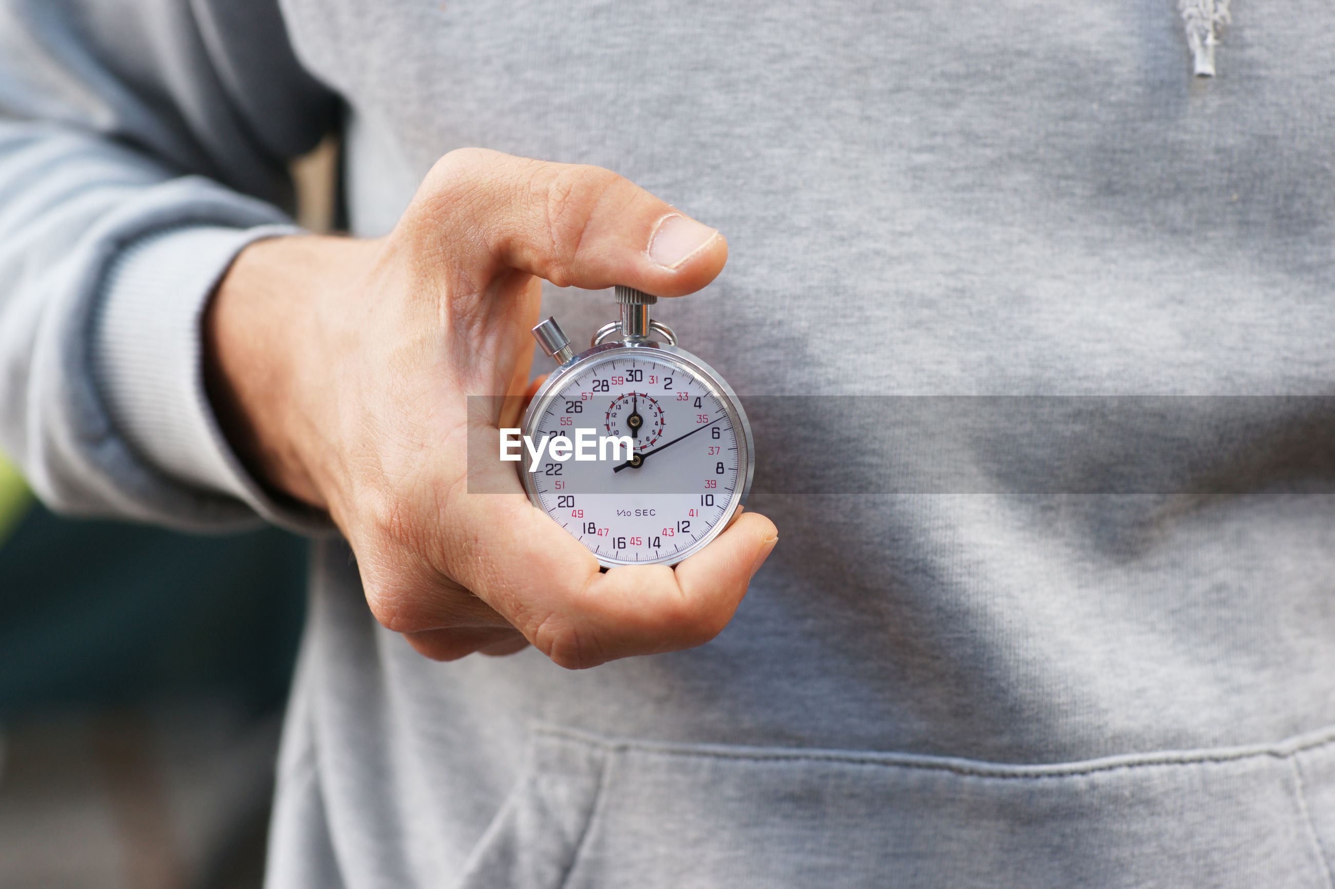 Midsection of man holding stopwatch