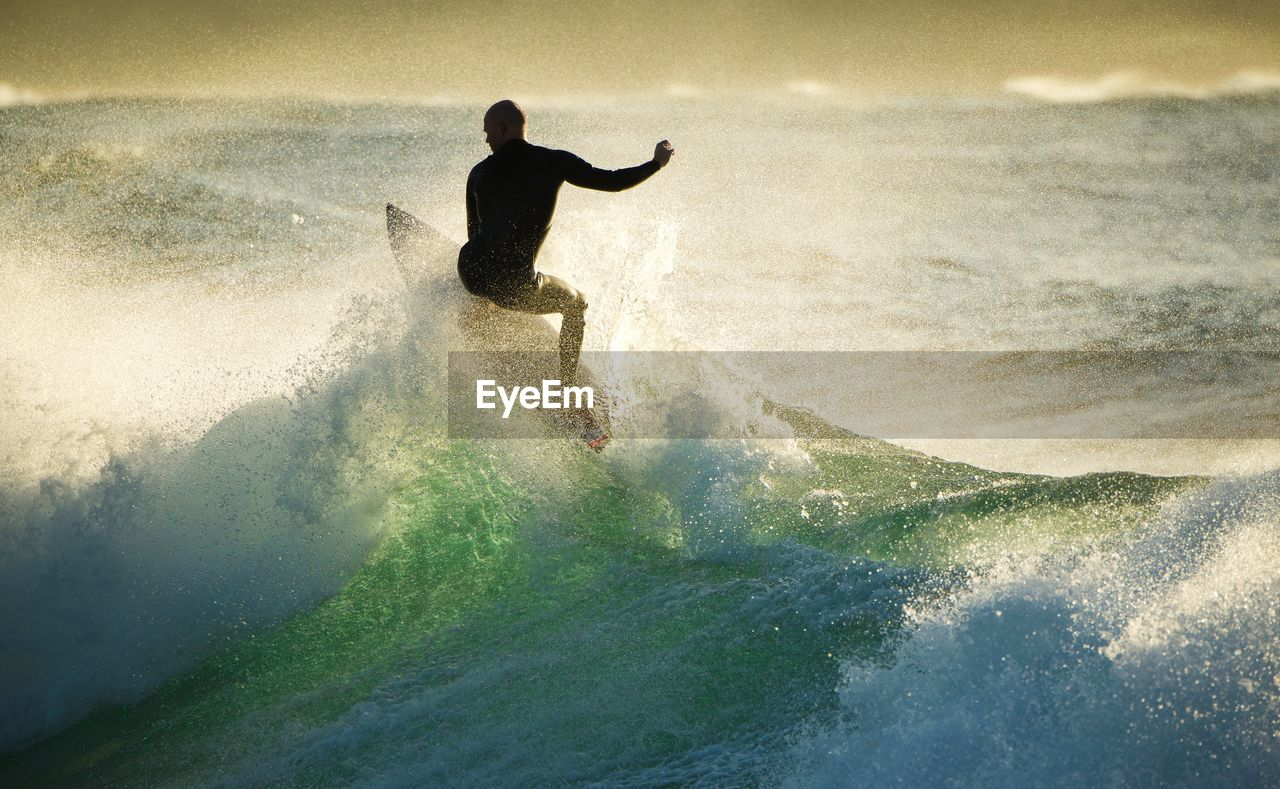 one person, sea, surfboard, adventure, wave, surfing, one man only, water, motion, outdoors, day, leisure activity, real people, full length, nature, vacations, sky, men, only men, horizon over water, extreme sports, beauty in nature, adult, adults only, people