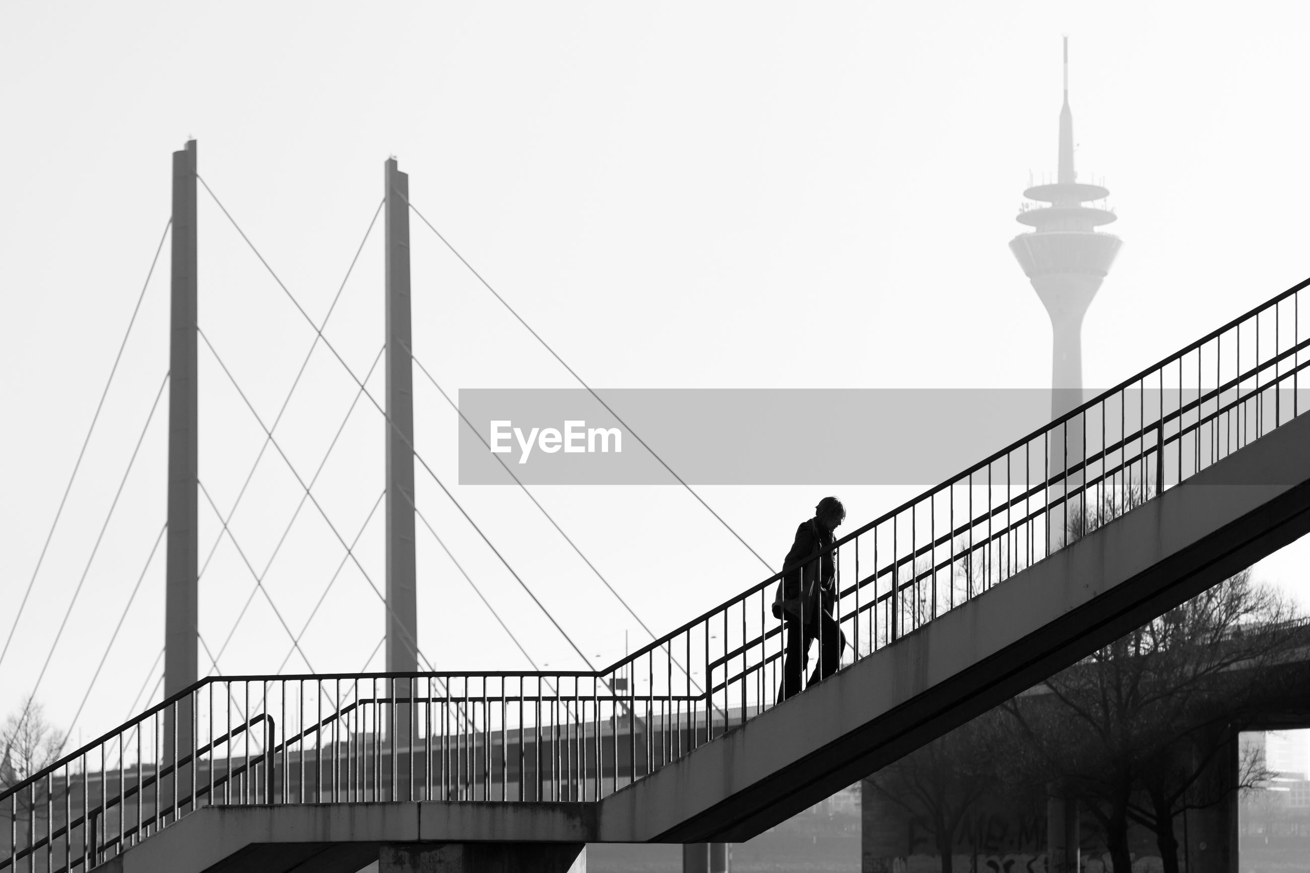three quarter length, built structure, architecture, real people, railing, travel destinations, bridge - man made structure, connection, tourism, clear sky, city, outdoors, sky, standing, full length, suspension bridge, leisure activity, day, men, togetherness, people