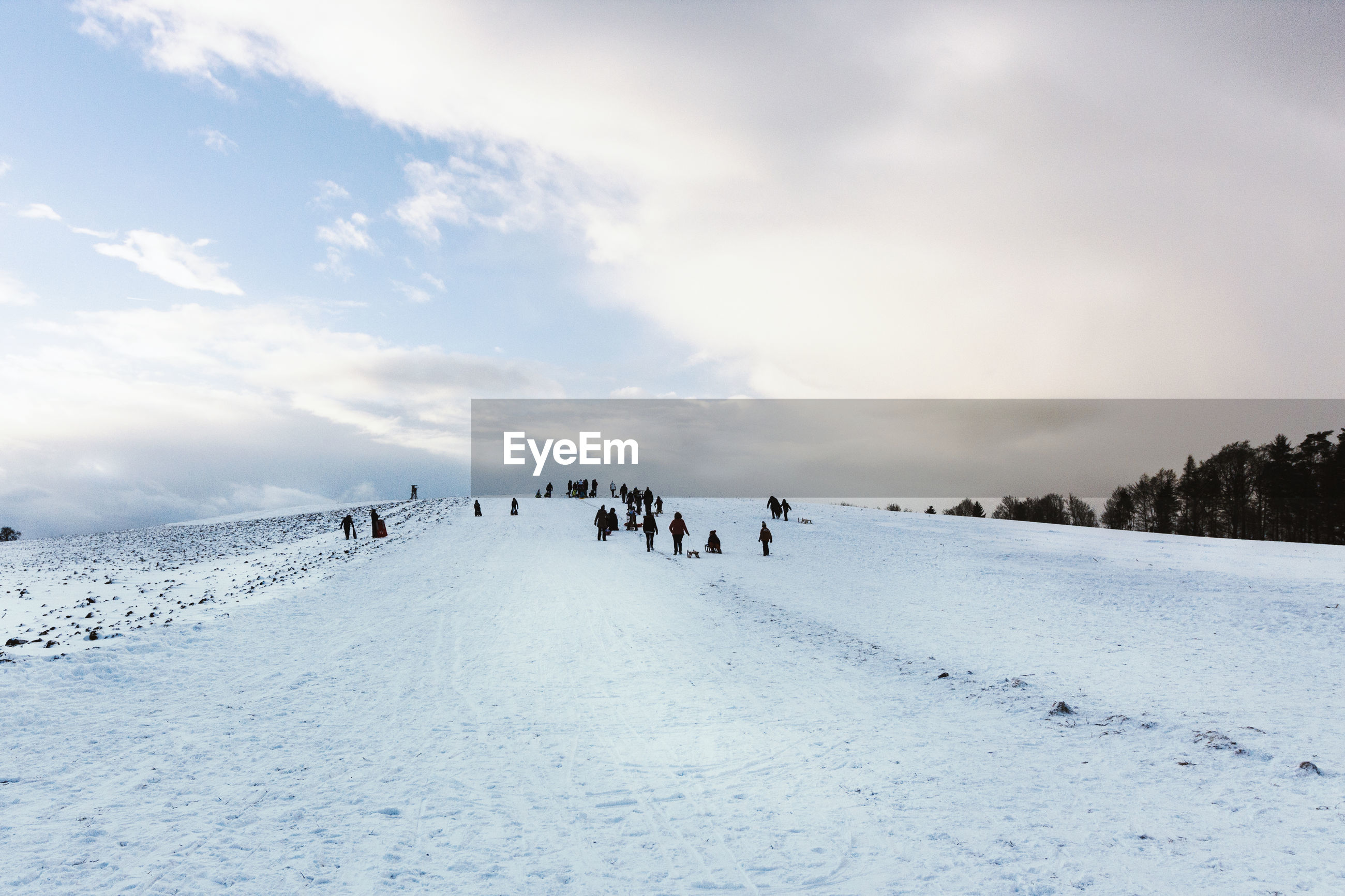 People on snowy landscape against sky during winter