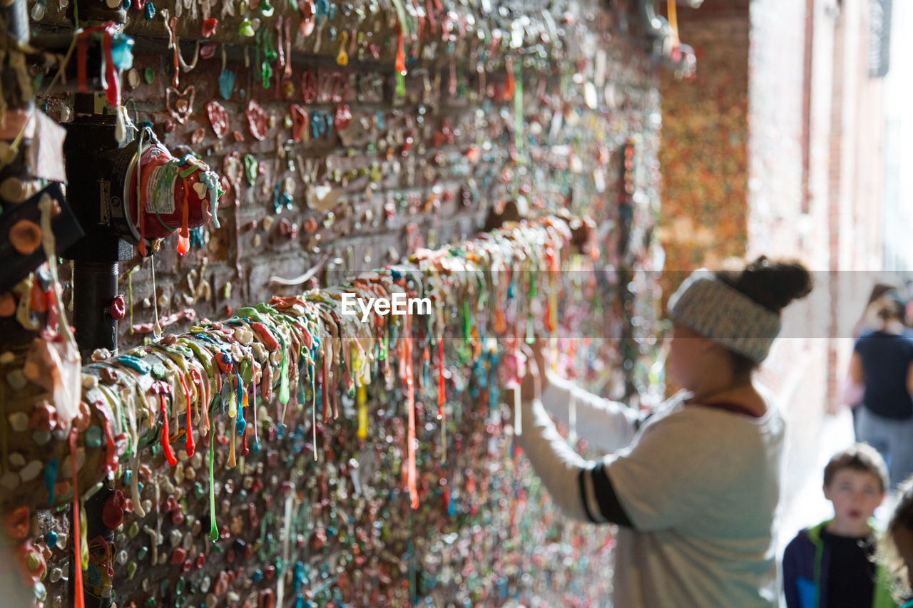 Side View Of Woman Standing By Gum Wall