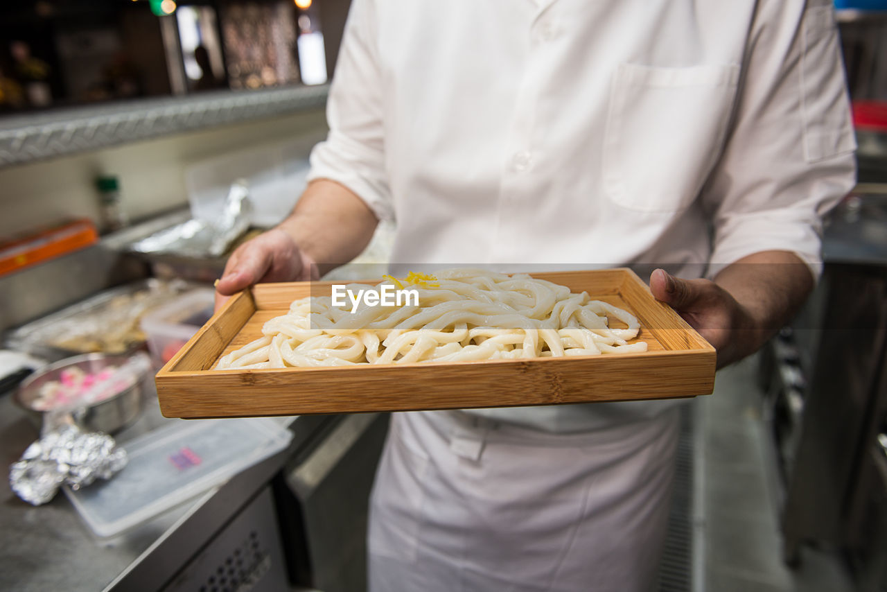 Midsection Of Chef Holding Tray Of Noodles