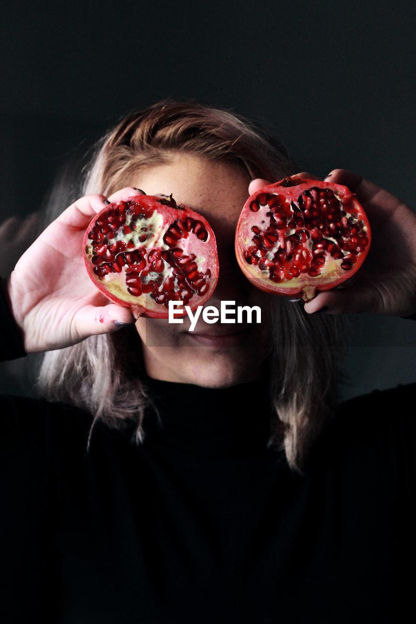 Woman Holding Halved Pomegranate Against Black Background