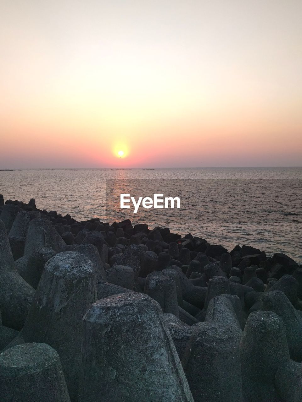 sea, sunset, water, beauty in nature, horizon over water, scenics, tranquil scene, tranquility, nature, beach, sun, idyllic, sky, rock - object, no people, outdoors, pebble, clear sky, pebble beach, day