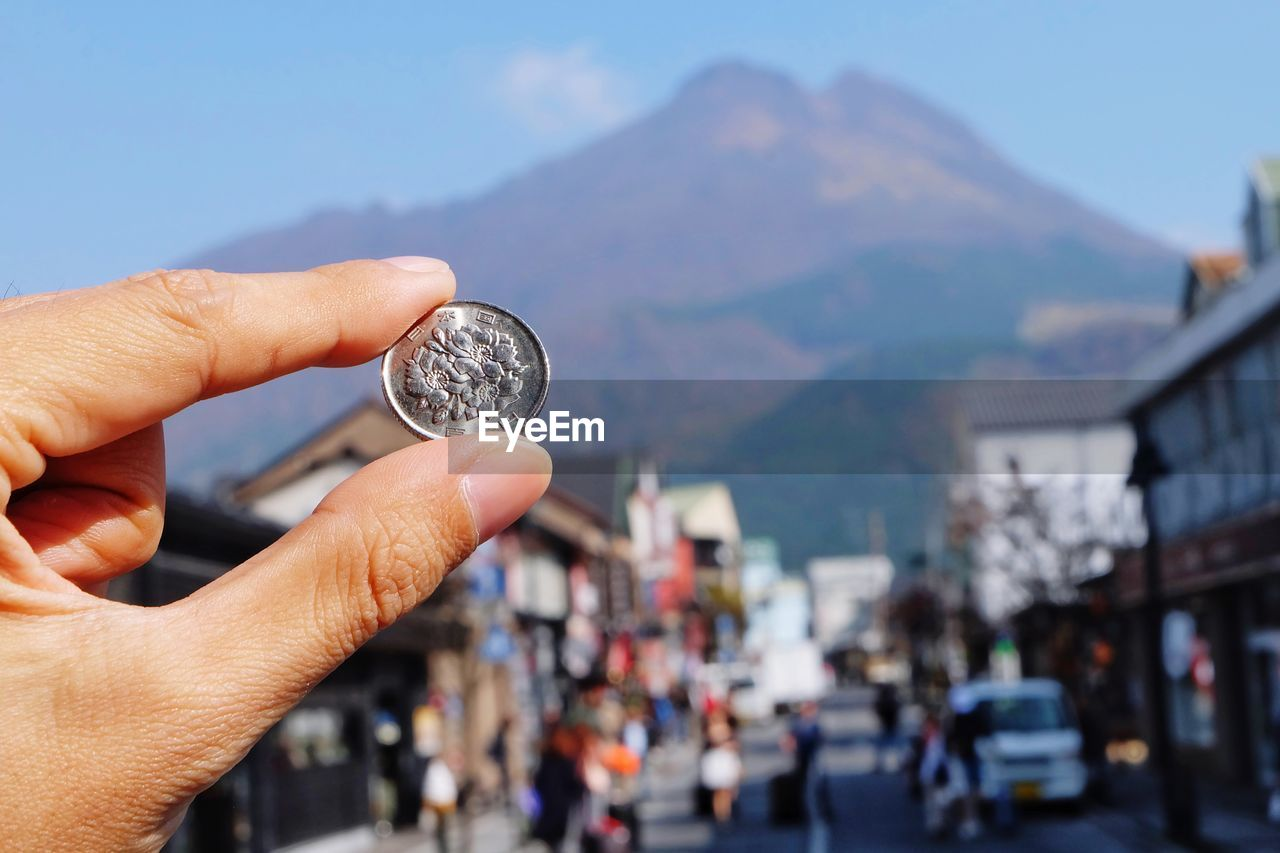 Cropped Hand Holding Coin Against Mountain