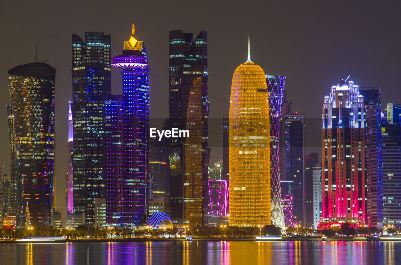 building exterior, built structure, architecture, building, night, illuminated, office building exterior, city, skyscraper, water, waterfront, tall - high, modern, landscape, urban skyline, sky, cityscape, travel destinations, tower, no people, financial district, outdoors, luxury