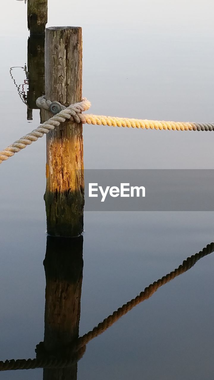 Rope Attached To Wooden Post In Lake