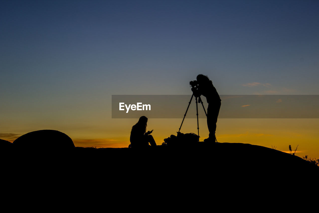 SILHOUETTE OF PHOTOGRAPHING AGAINST SUNSET SKY