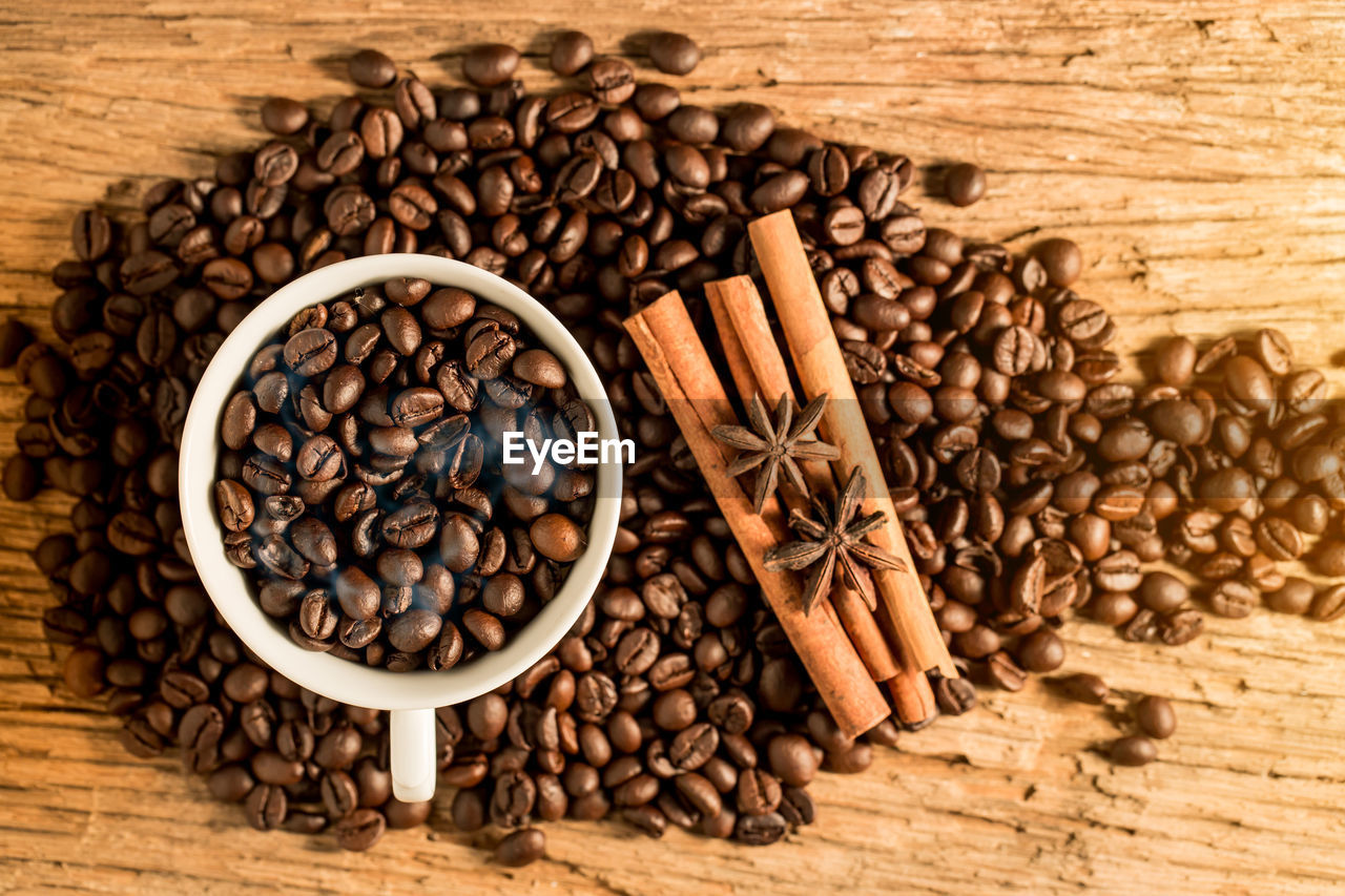 Close-Up Of Coffee Beans In Cup With Spices On Wooden Table