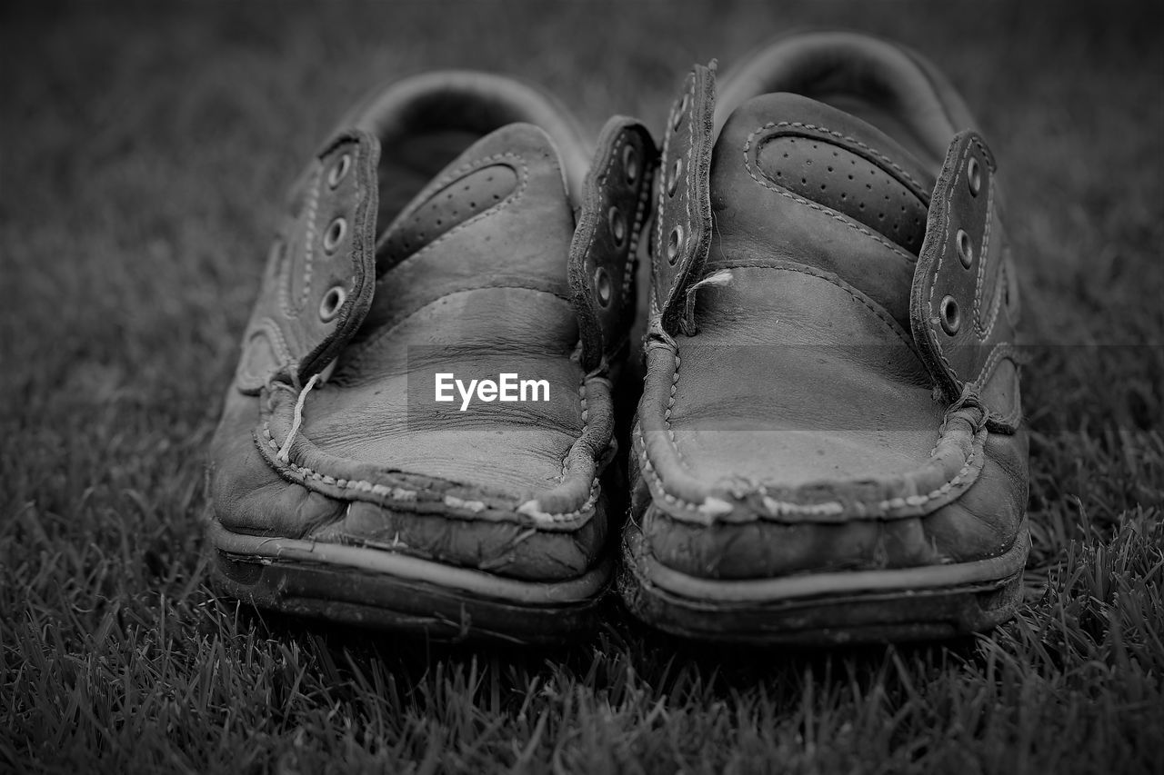Close-up of old shoes on field