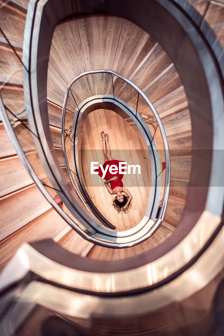 Directly Above Shot Of Woman Lying On Floor Amidst Spiral Staircase