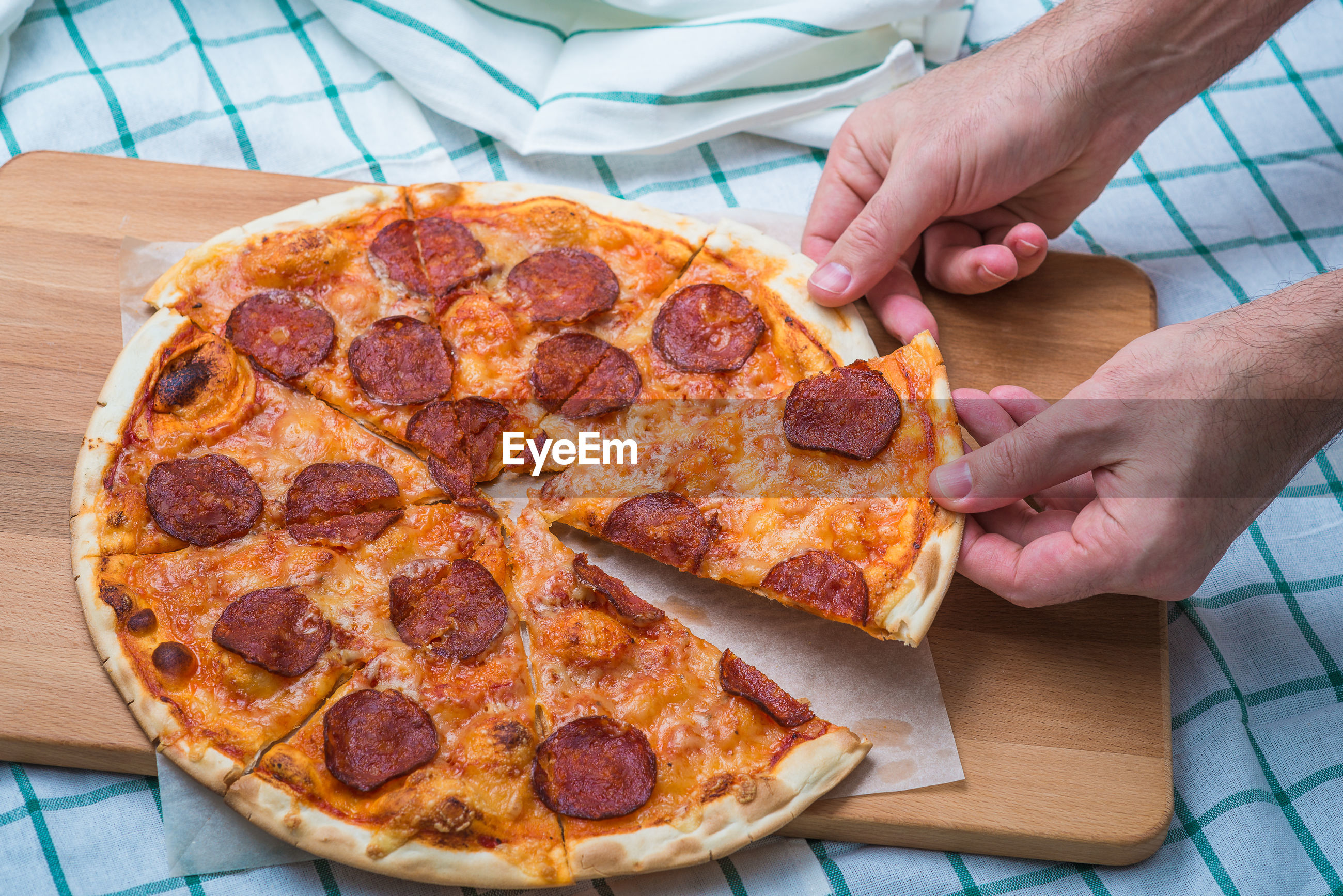 Cropped hands of man picking pizza slices
