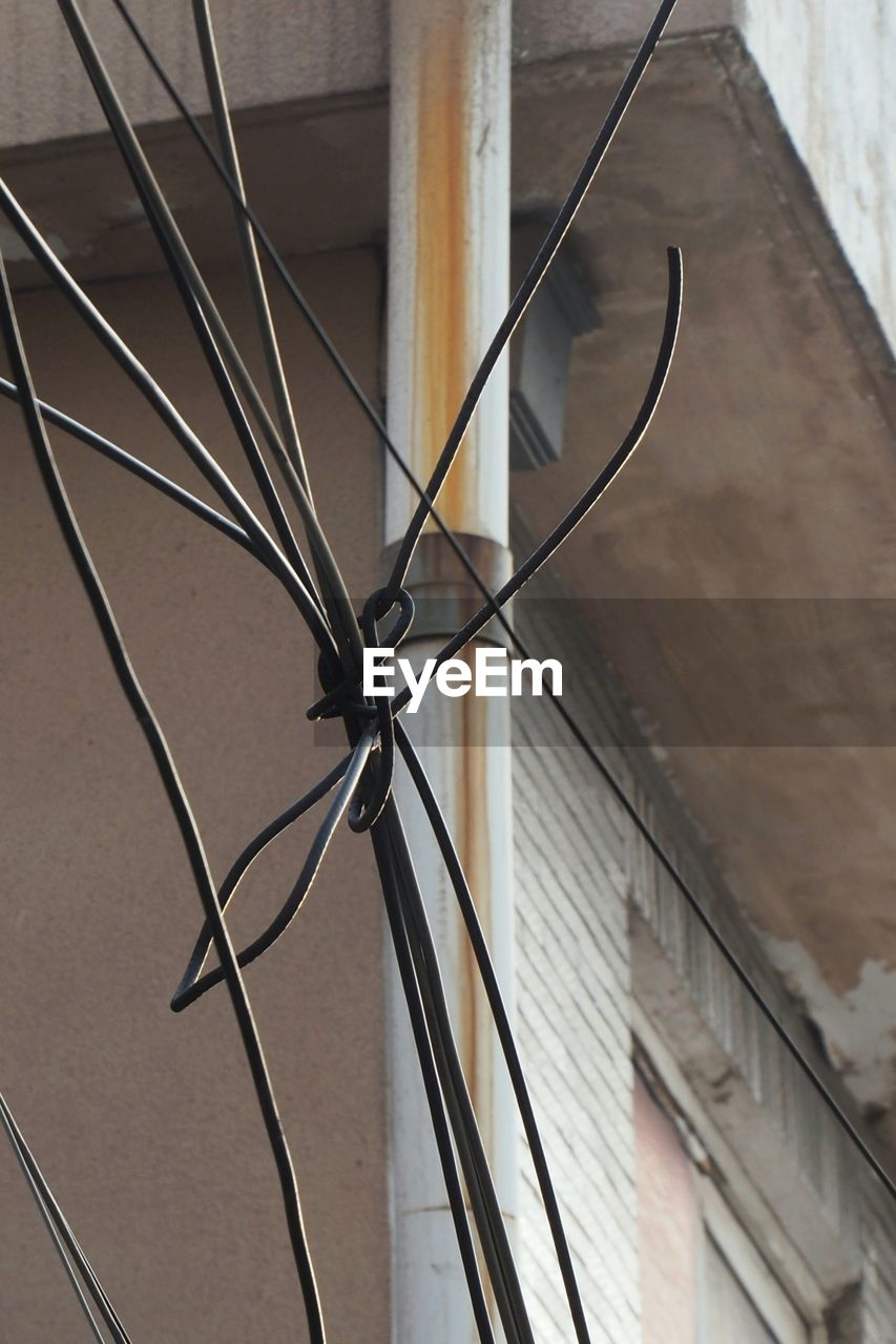 no people, close-up, metal, focus on foreground, wall - building feature, day, built structure, outdoors, technology, connection, low angle view, architecture, cable, wood - material, flooring, pattern, security, safety, spoke