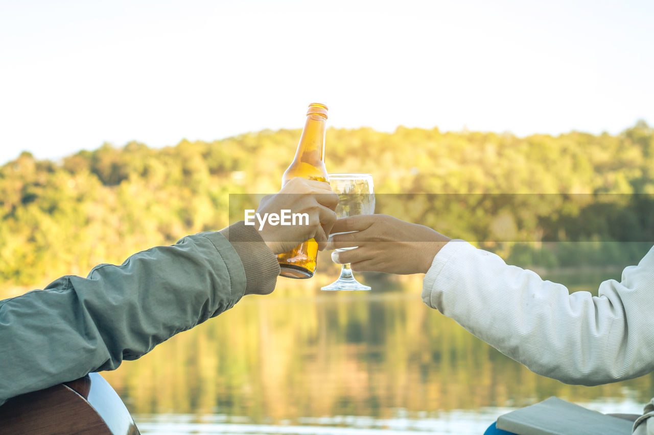 Cropped Hands Of Friends Toasting While Sitting Against Lake