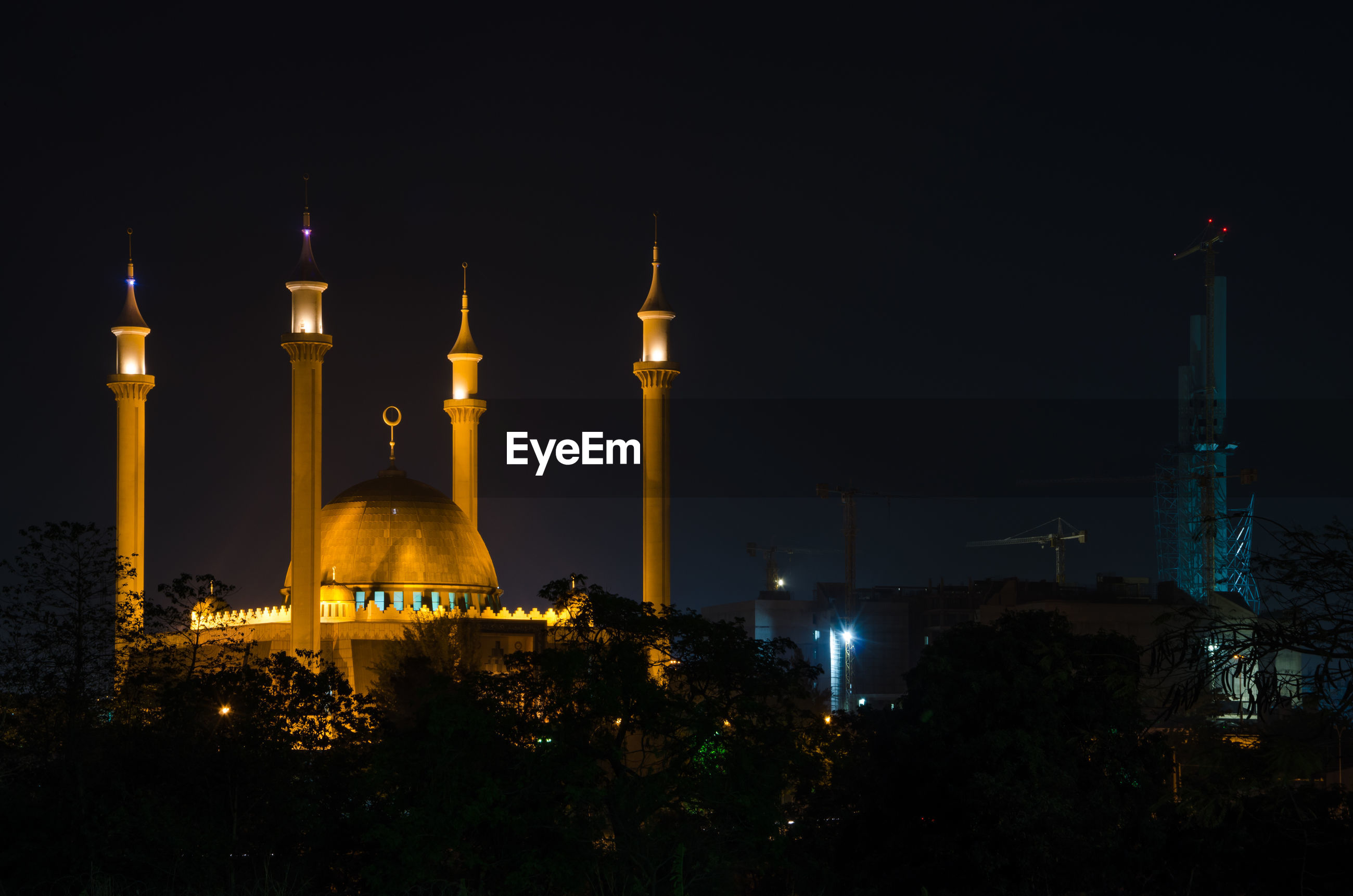 Illuminatednational mosque of abuja against sky during night