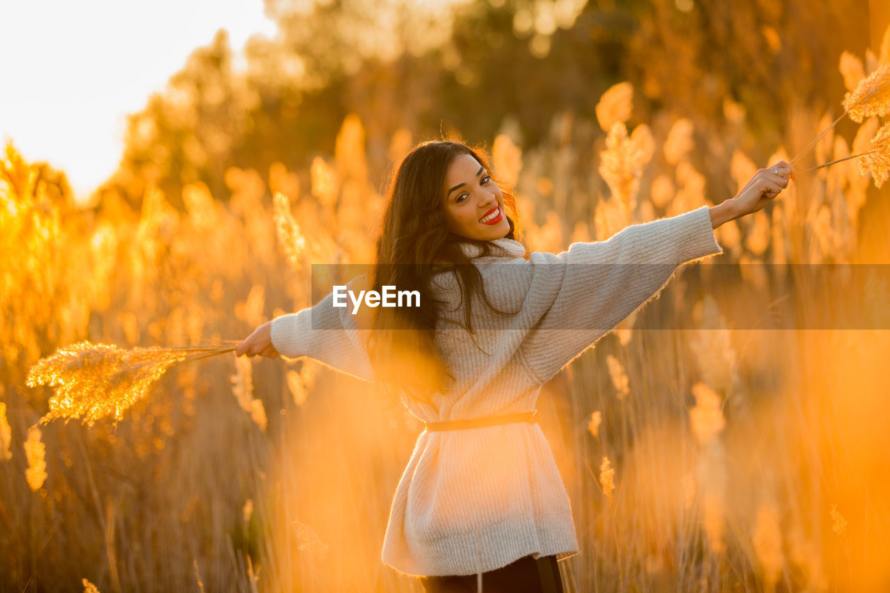 one person, young adult, human arm, young women, real people, leisure activity, standing, lifestyles, women, limb, plant, long hair, land, casual clothing, three quarter length, field, hairstyle, arms raised, adult, smiling, arms outstretched, hair, beautiful woman, outdoors, freedom, human limb, change