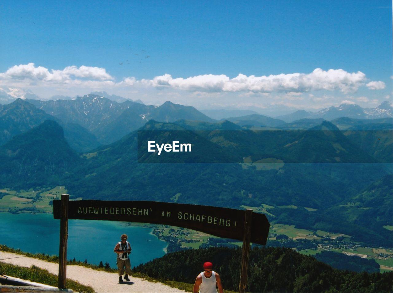 PEOPLE STANDING ON MOUNTAIN PEAK AGAINST SKY