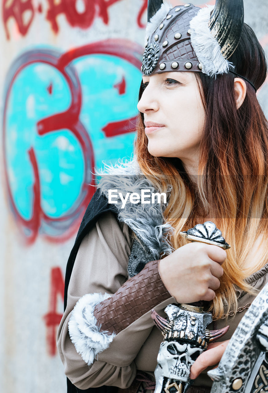 young adult, one person, lifestyles, real people, young women, leisure activity, portrait, clothing, long hair, hairstyle, hair, casual clothing, fashion, looking, looking away, waist up, day, graffiti, front view, beautiful woman, contemplation, outdoors, scarf, warm clothing