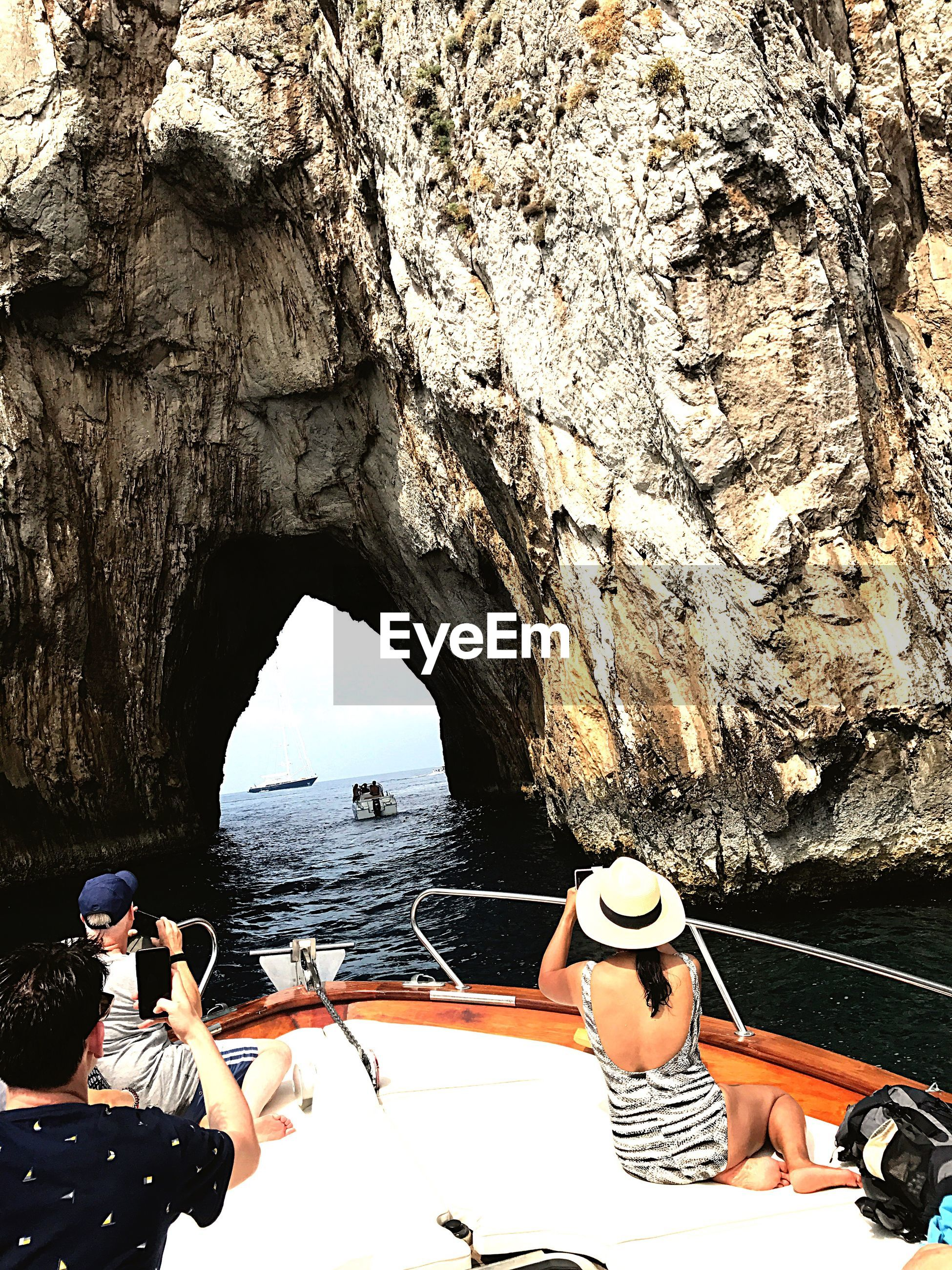 People sitting on boat sailing by rock formation in sea