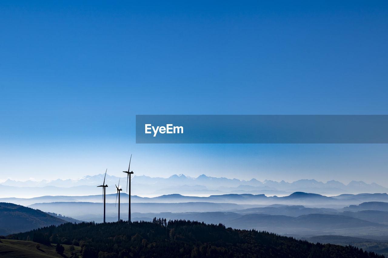 Windmills On Mountain Against Blue Sky
