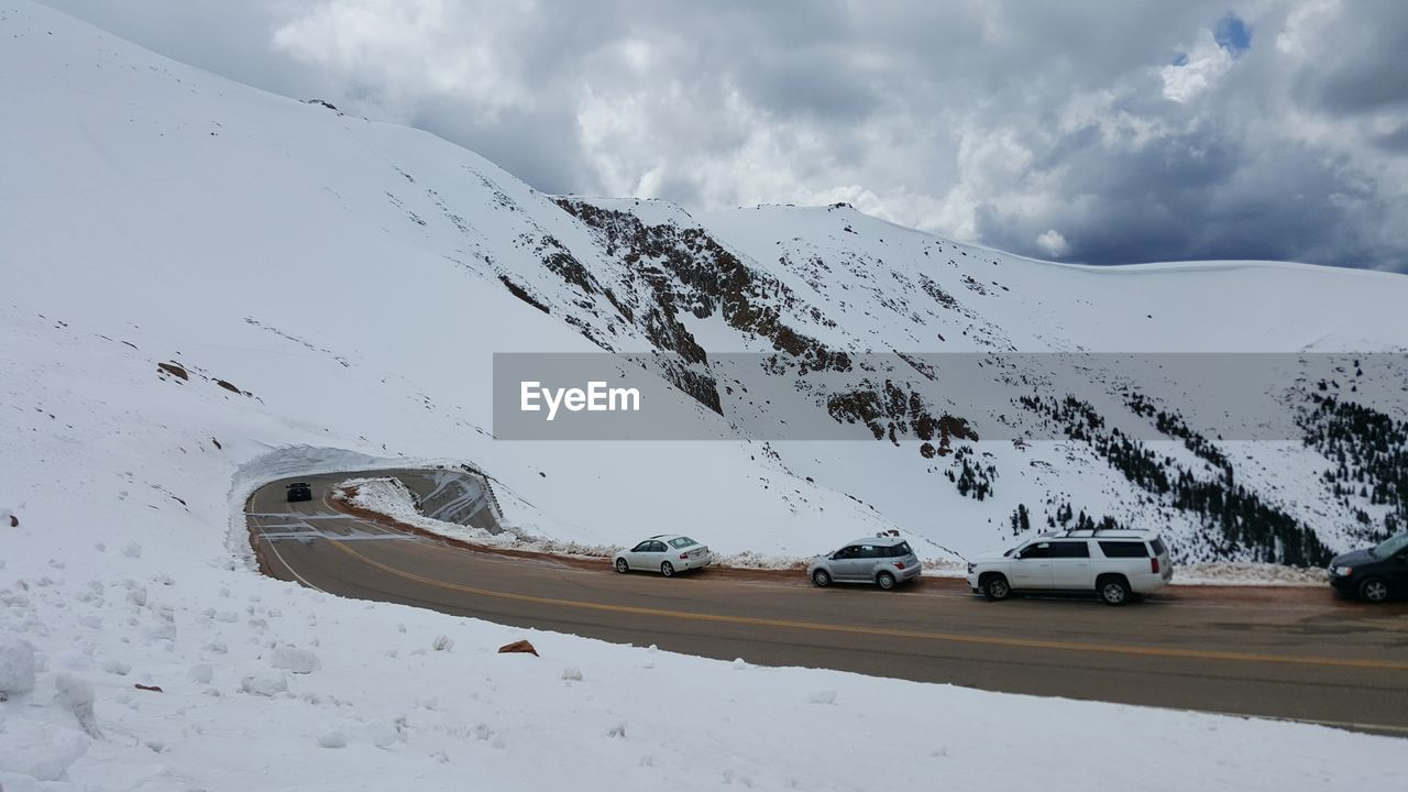 Cars Moving On Road By Snow Covered Mountain