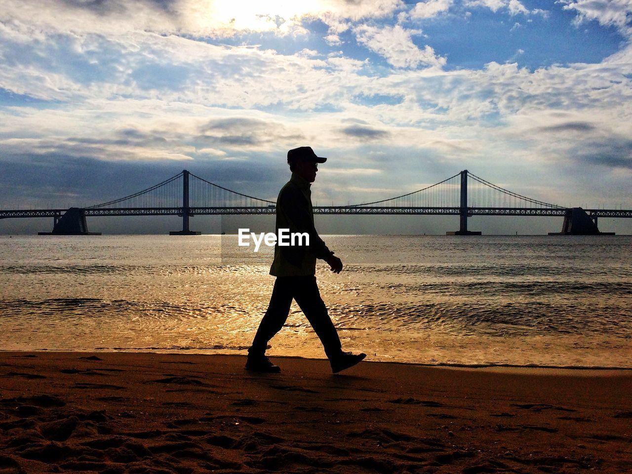 Full length of man walking on shore against bridge at beach