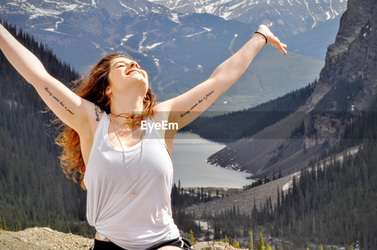 Happy beautiful woman with arms raised standing against mountains