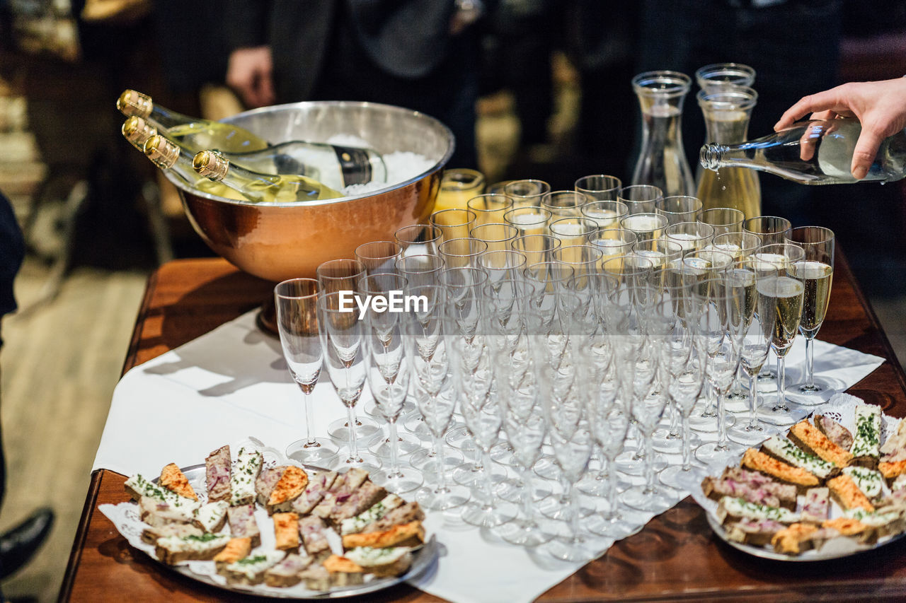 food and drink, food, table, freshness, drink, refreshment, incidental people, real people, glass, indoors, alcohol, business, one person, ready-to-eat, restaurant, sweet, household equipment, sweet food, unrecognizable person, bottle, hand, tray