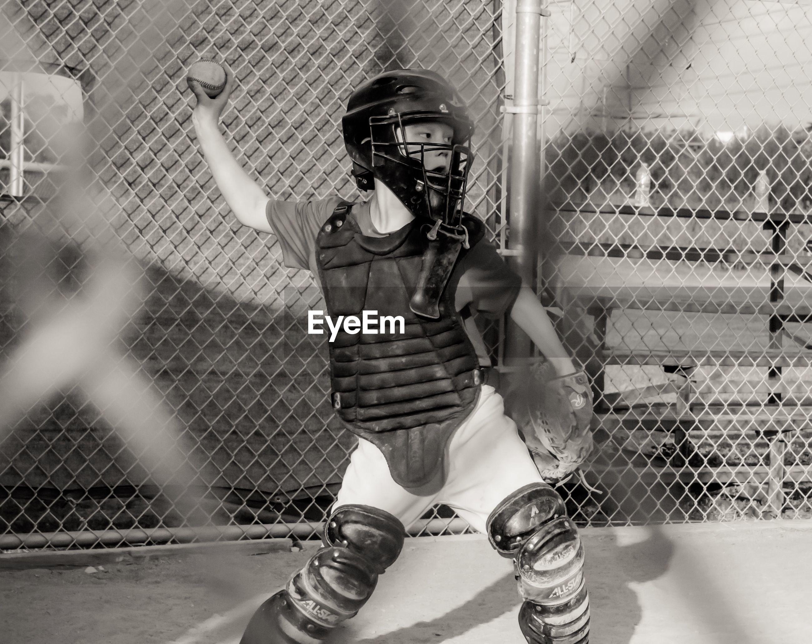 Boy throwing ball while playing baseball