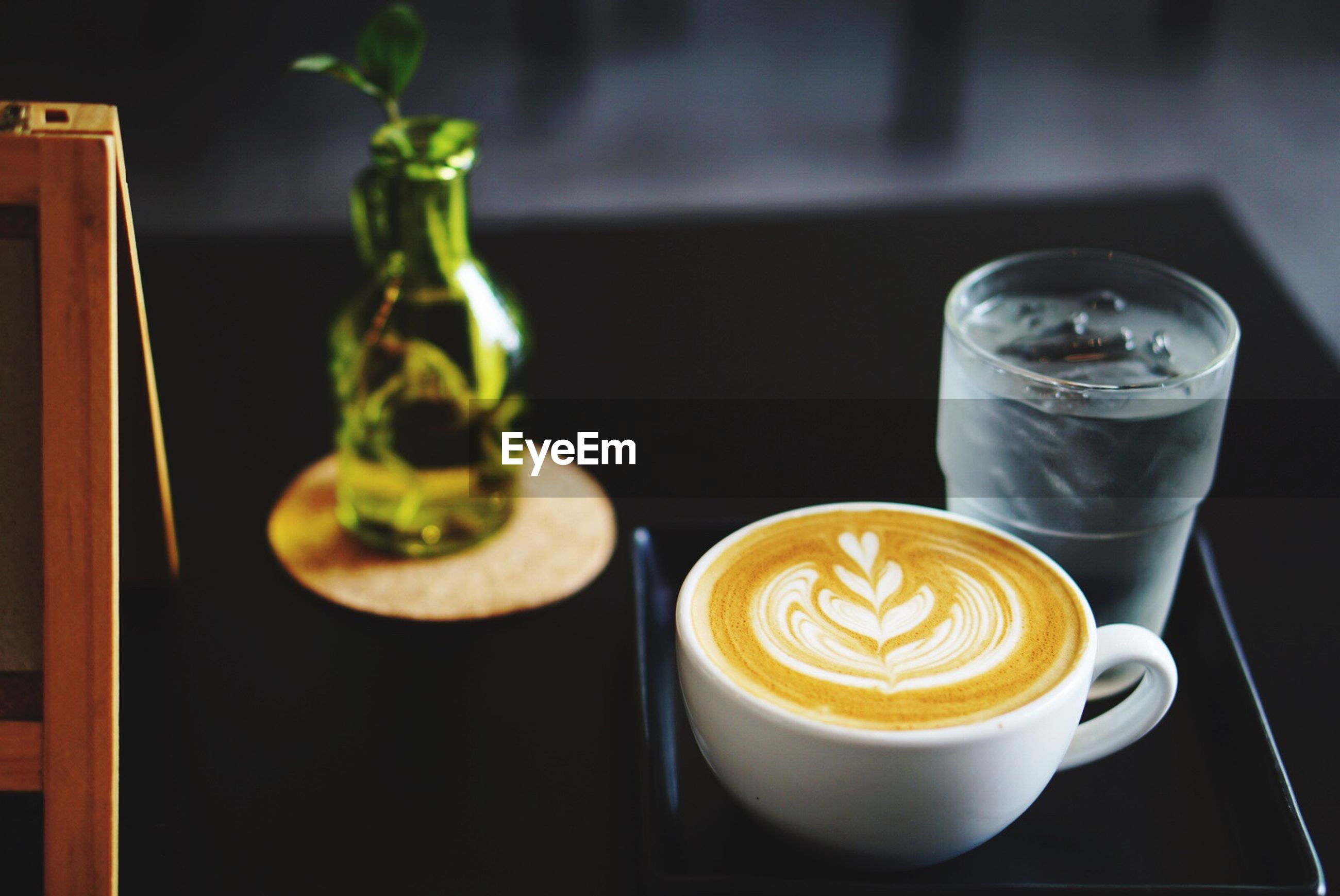 High angle view of fresh coffee served with water on table