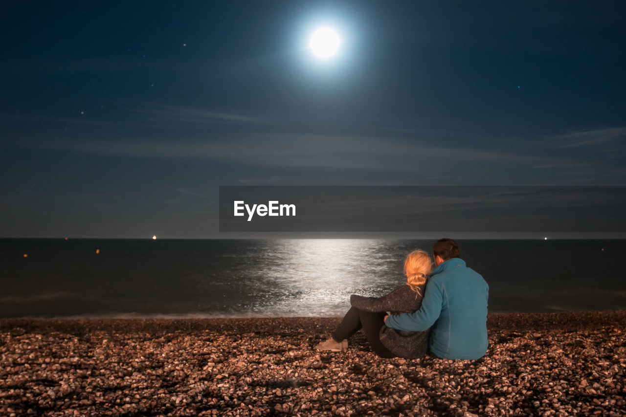 Couple Sitting On Shore Against Sky At Night