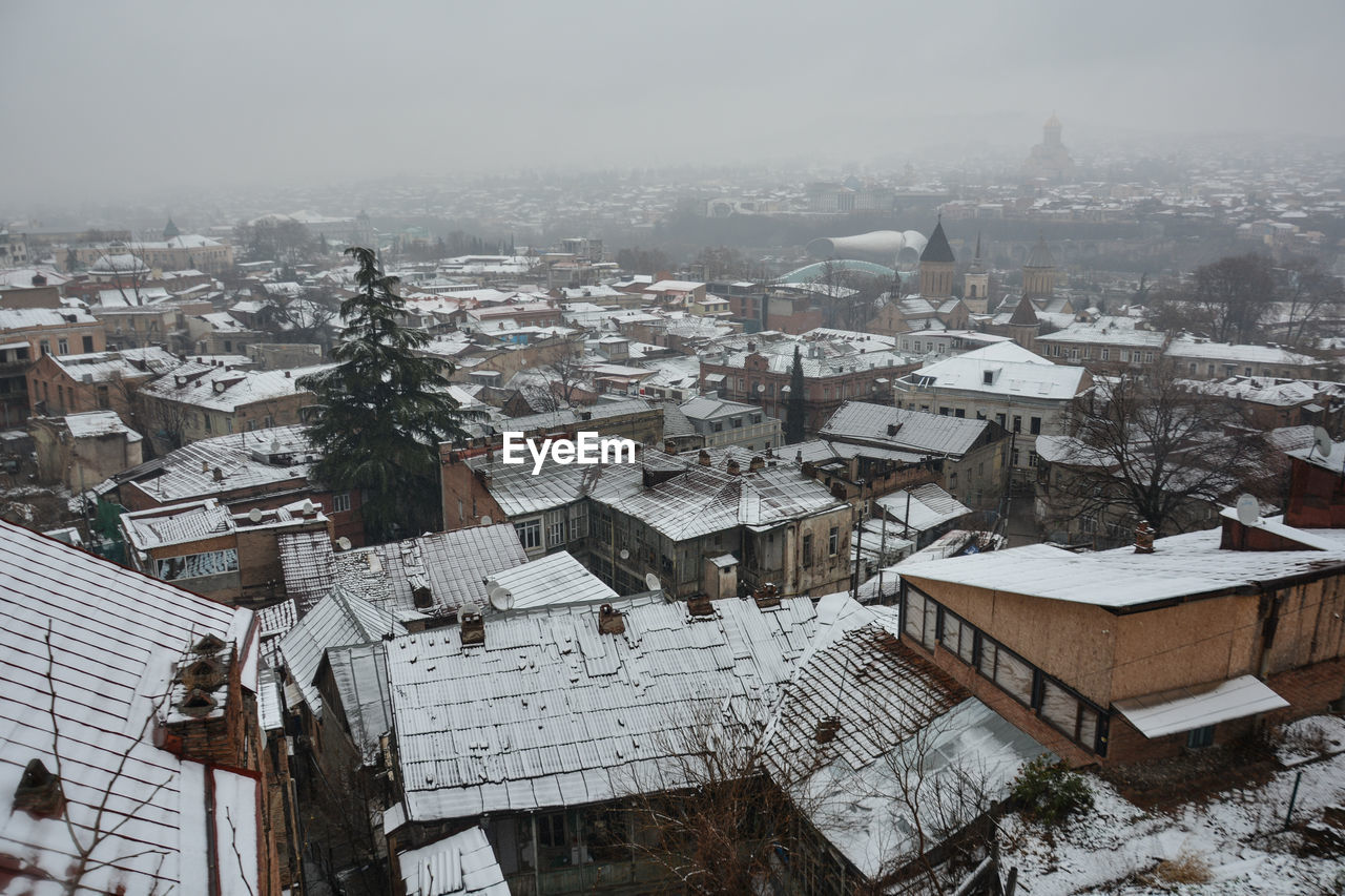 HIGH ANGLE VIEW OF TOWNSCAPE AGAINST SNOW COVERED HOUSES