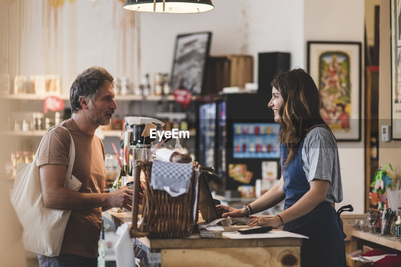 two people, real people, adult, customer, casual clothing, occupation, small business, business, women, young adult, men, standing, retail, indoors, people, focus on foreground, young women, three quarter length, store, entrepreneur, buying