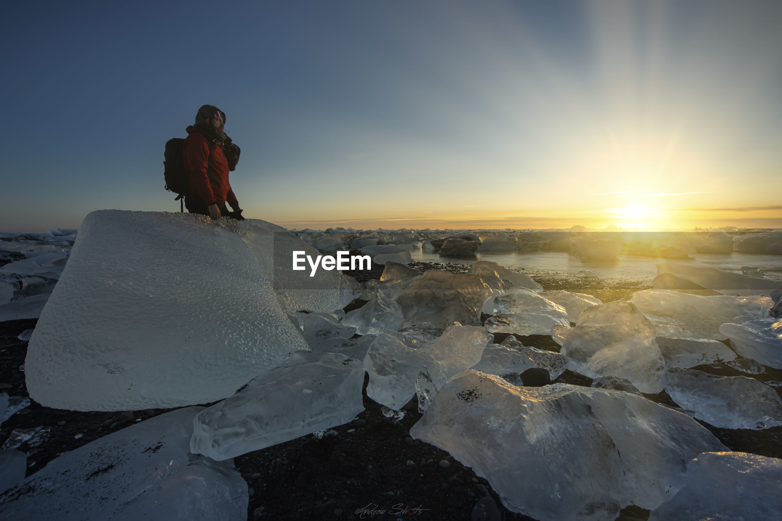 Man standing over ice by frozen lake against sky during sunset