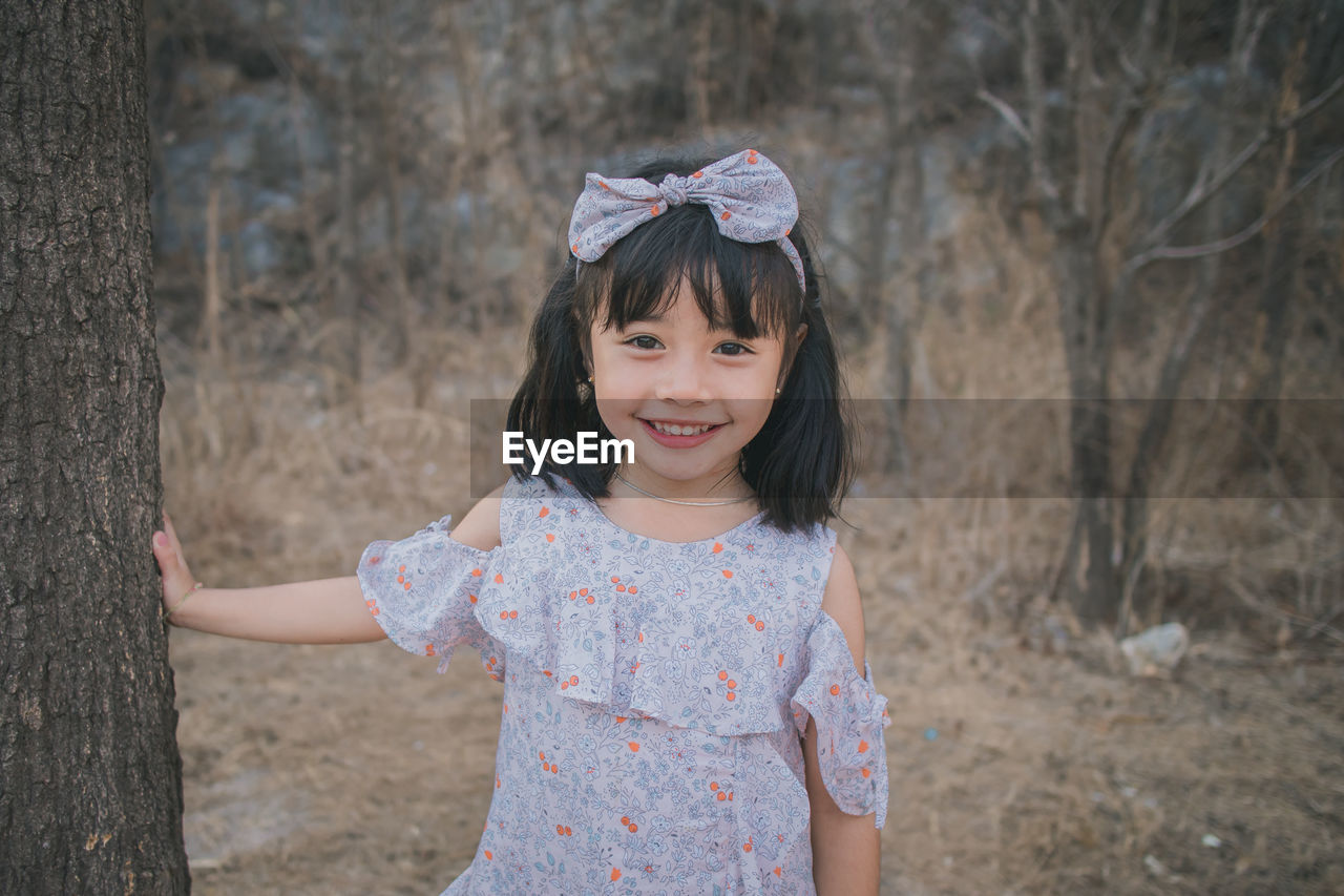 PORTRAIT OF A SMILING GIRL STANDING AGAINST TREES