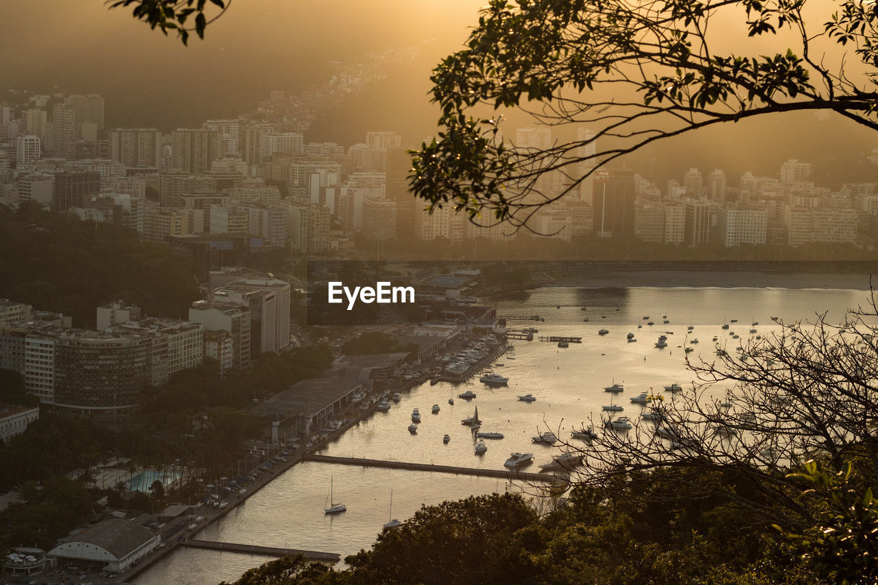 High Angle View Of Cityscape By River During Sunset