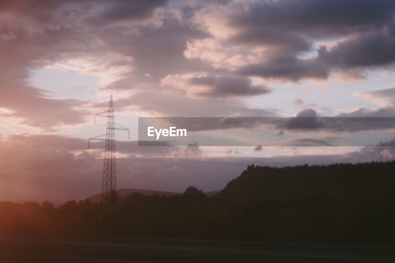 SILHOUETTE ELECTRICITY PYLON AGAINST CLOUDY SKY