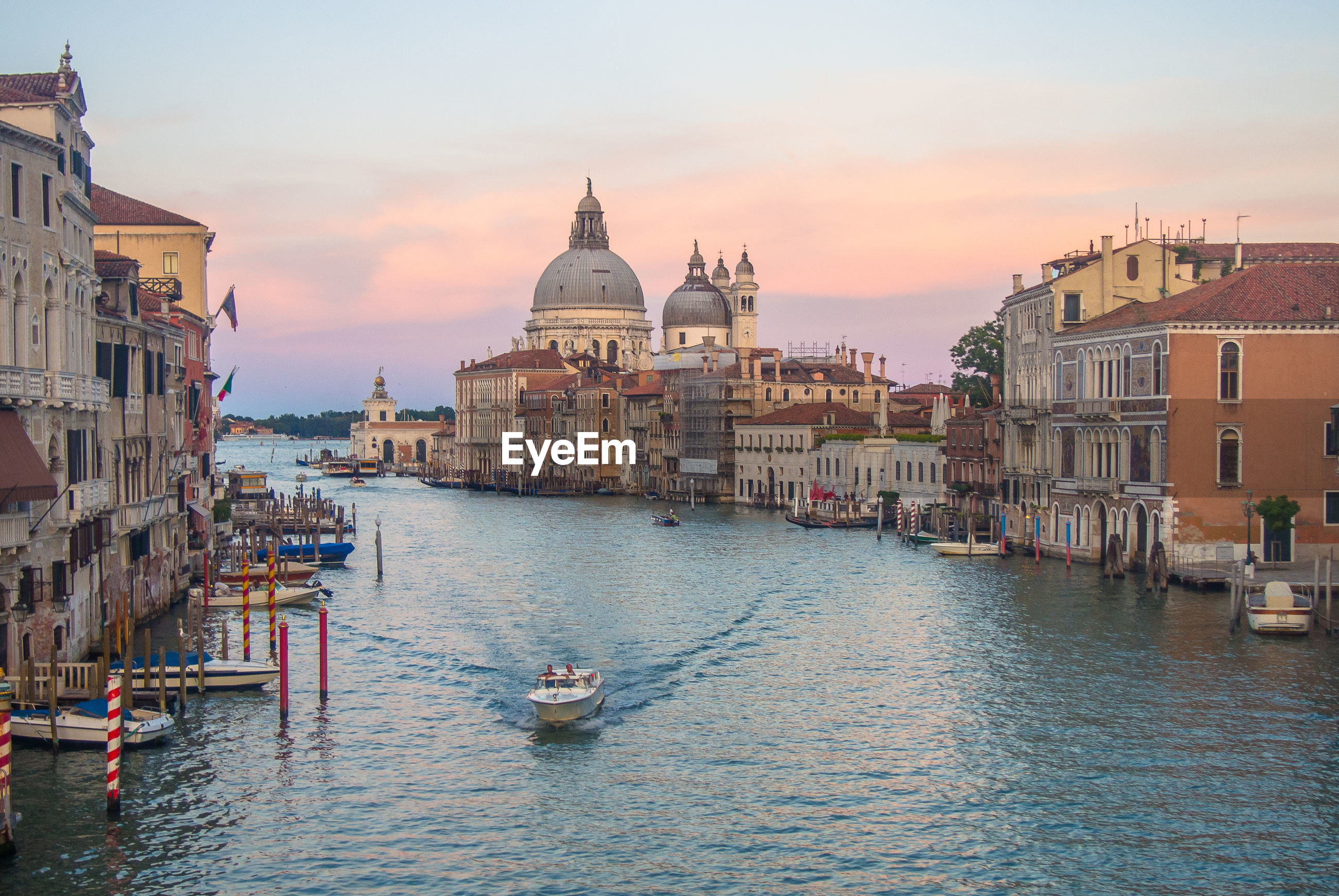 Motorboat sailing on grand canal by santa maria della salute against sky during sunset