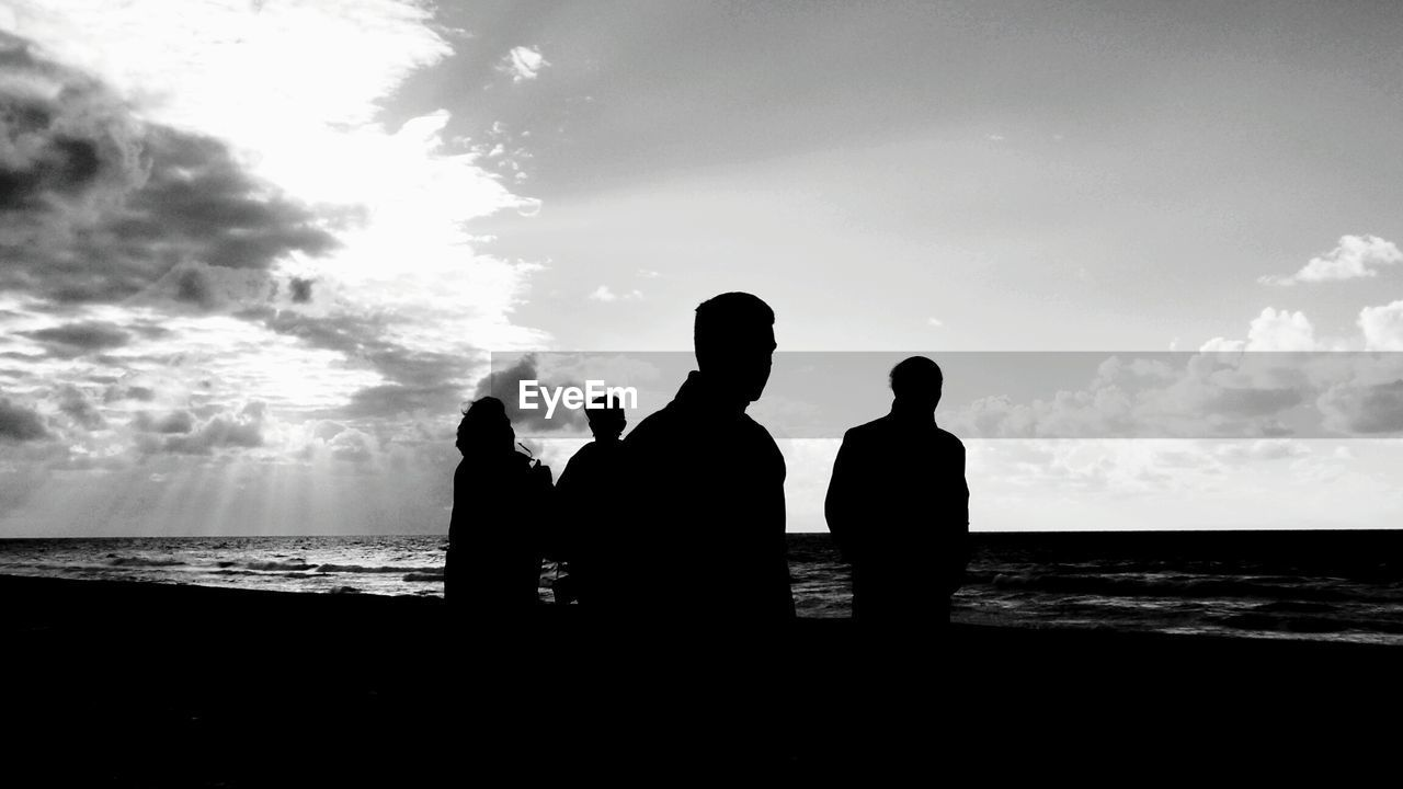 silhouette, sky, water, real people, men, togetherness, cloud - sky, sea, rear view, standing, beach, leisure activity, outdoors, horizon over water, scenics, friendship, lifestyles, nature, women, beauty in nature, bonding, day, people