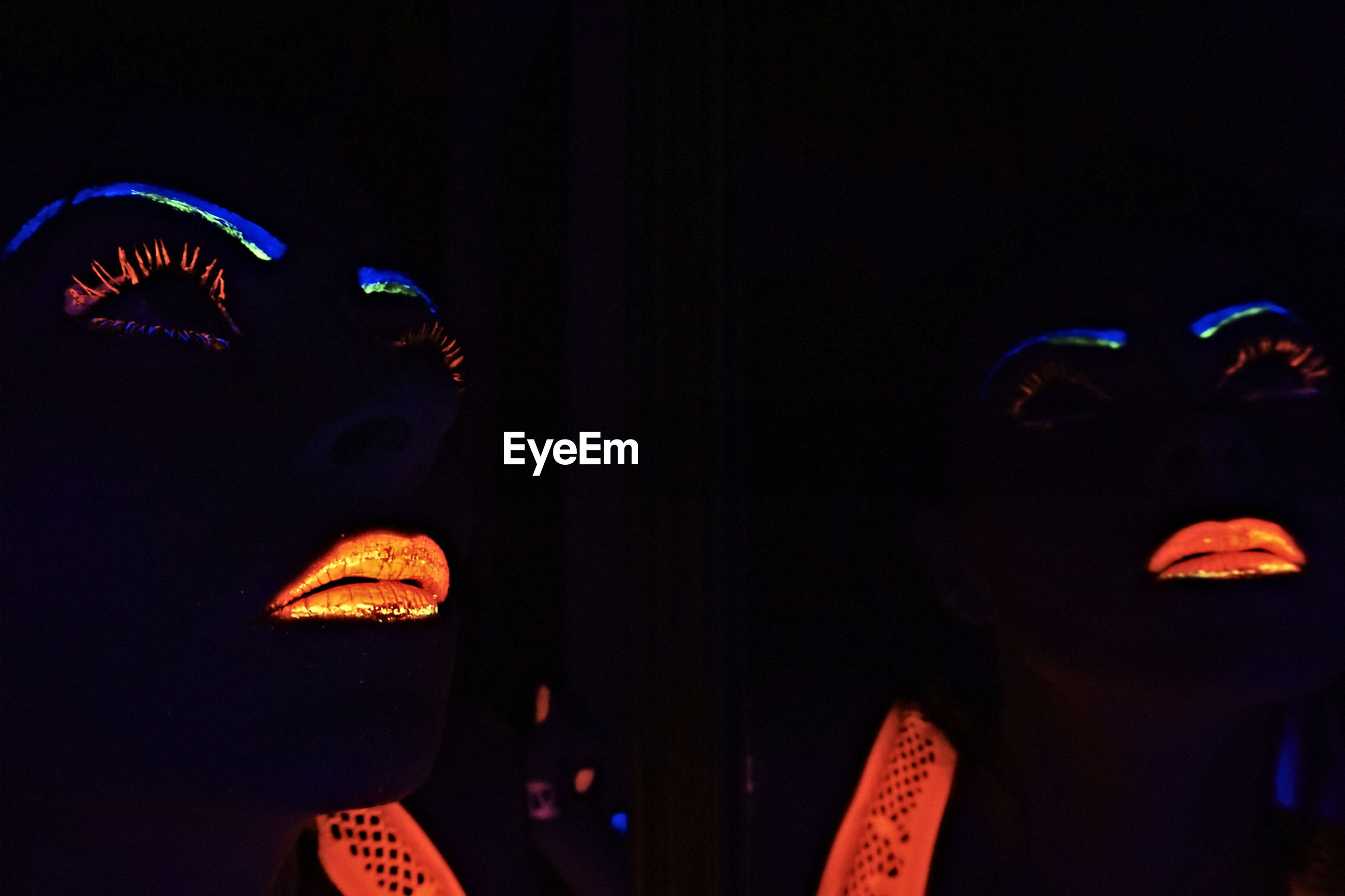 Reflection of woman with neon face paint on mirror