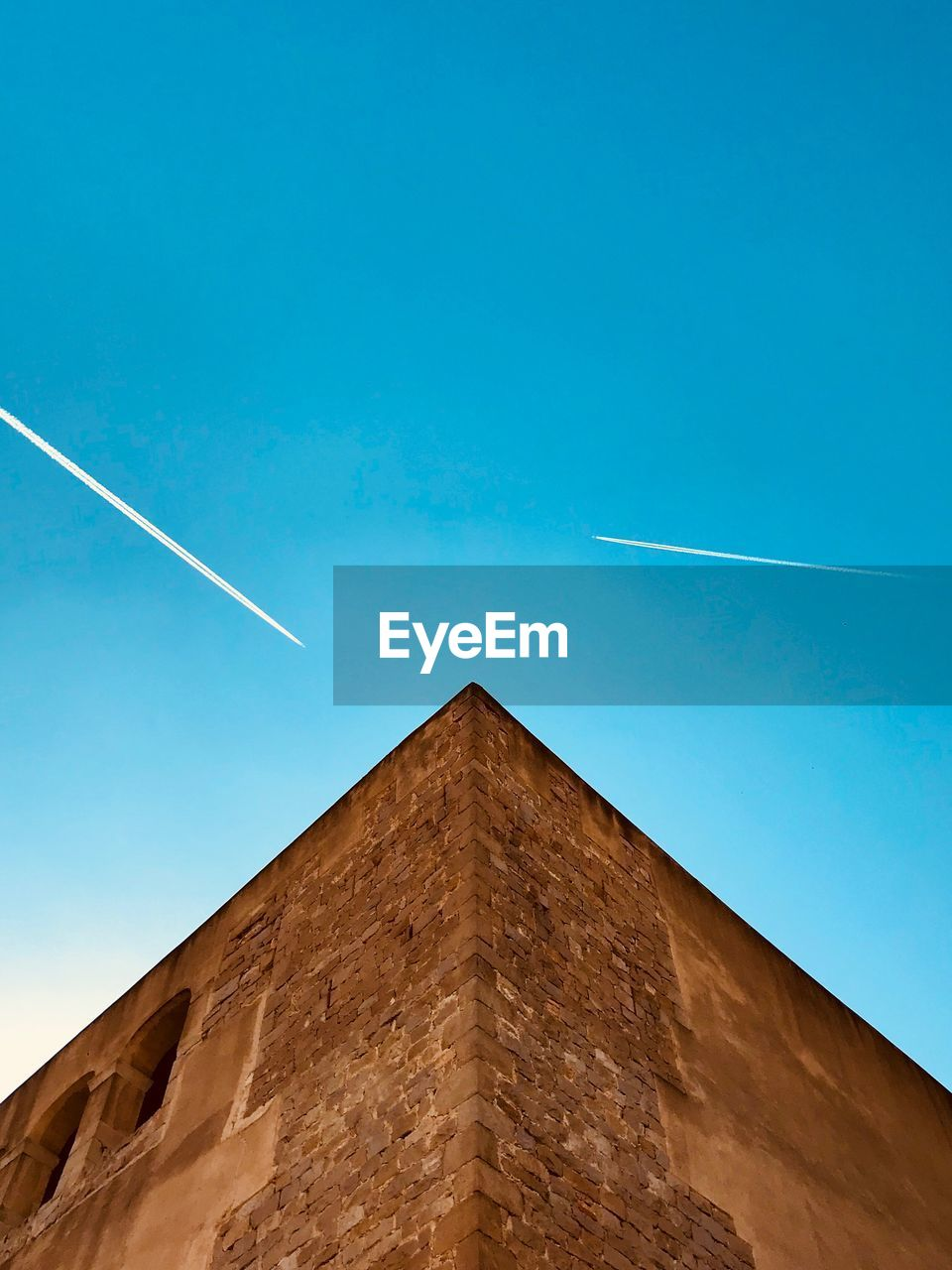 low angle view, vapor trail, sky, blue, clear sky, nature, architecture, no people, built structure, day, building exterior, air vehicle, copy space, outdoors, mode of transportation, sunlight, transportation, travel, airplane