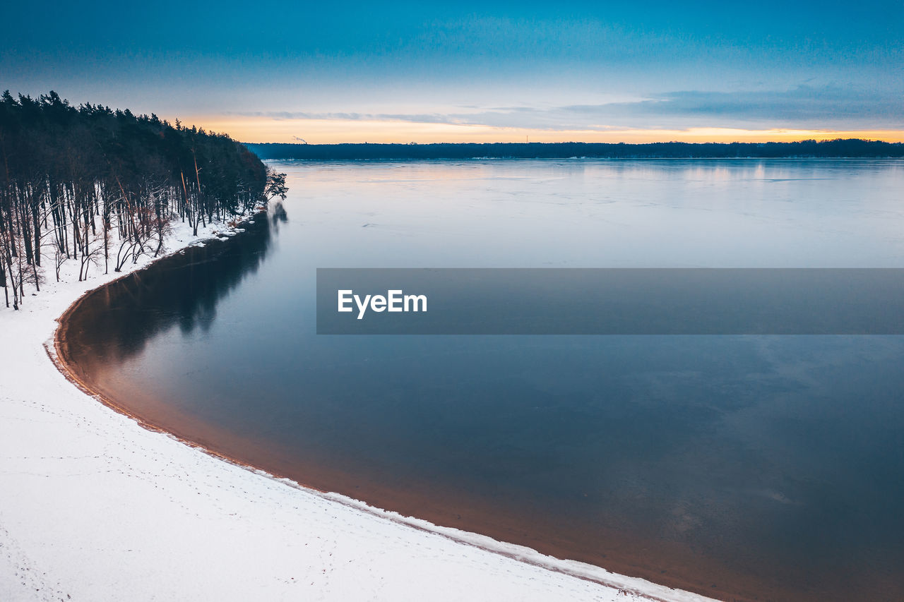 Scenic View Of Lake Against Sky During Sunset In Winter