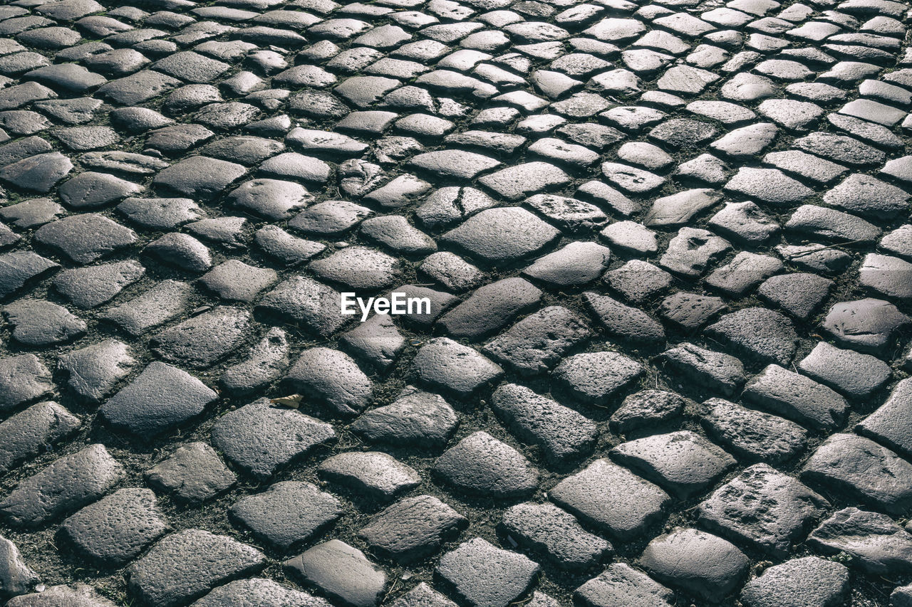 full frame, backgrounds, pattern, no people, textured, street, high angle view, day, cobblestone, close-up, repetition, stone, shape, solid, design, transportation, outdoors, gray, nature, stone - object, abstract, textured effect, paving stone, wheel, tire, pebble