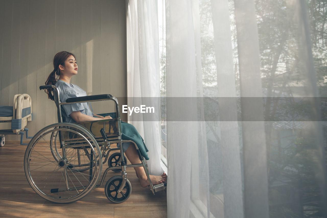 WOMAN LOOKING THROUGH WINDOW