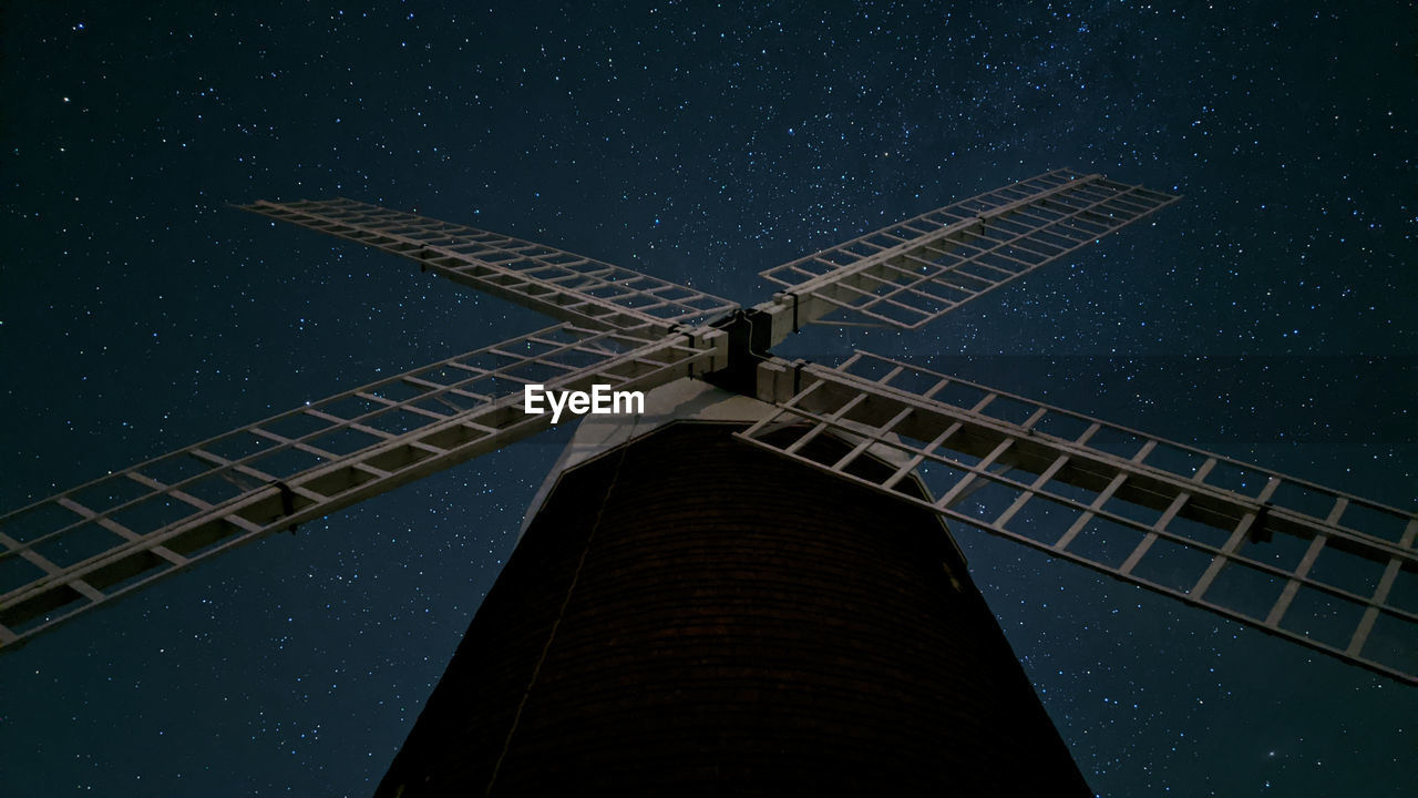 Low angle view of windmill against sky at night filled with stars