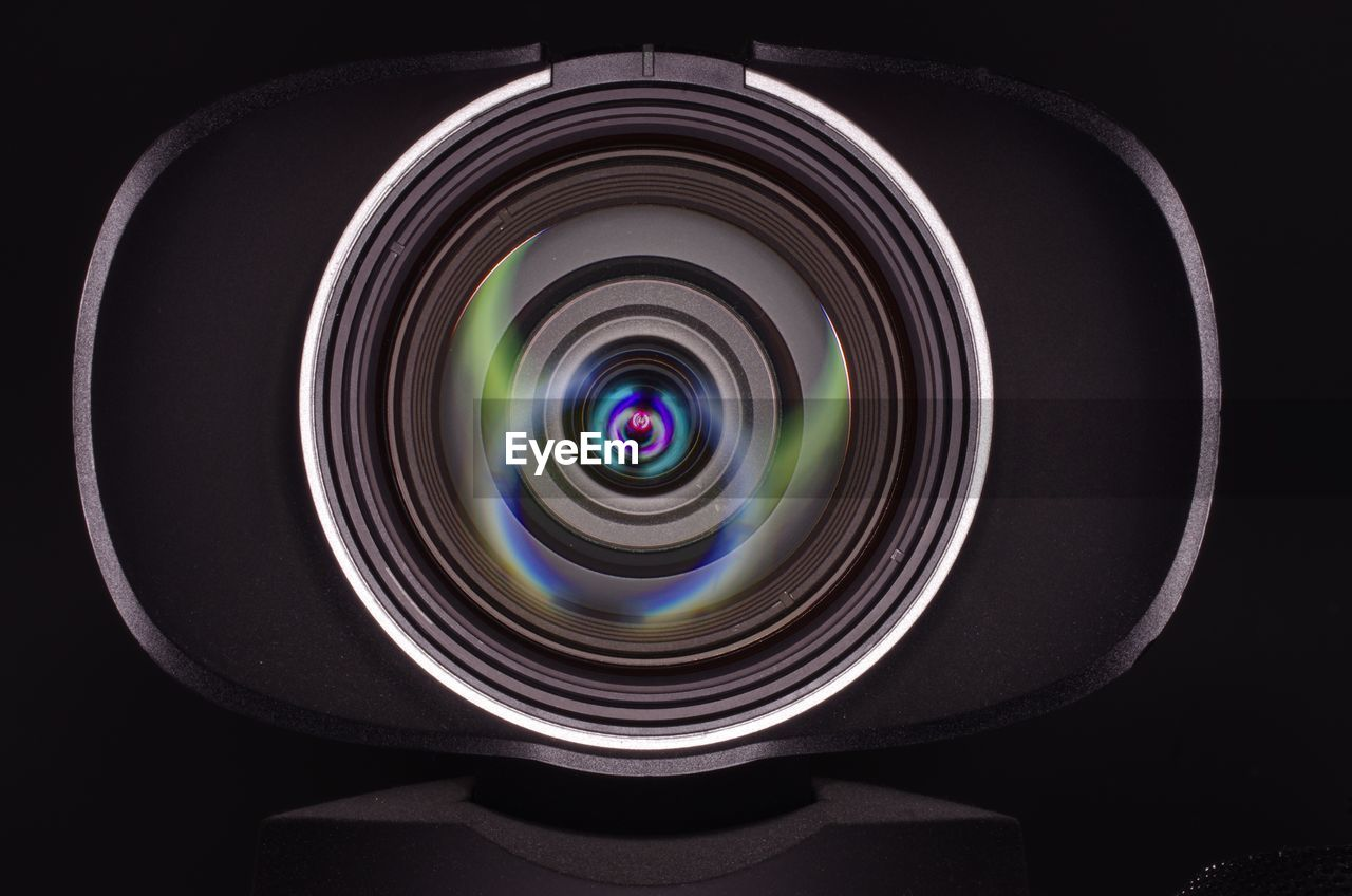 circle, geometric shape, indoors, studio shot, shape, close-up, technology, no people, black background, reflection, lens - optical instrument, photographic equipment, photography themes, camera - photographic equipment, multi colored, digital camera, directly above, glass - material, black color, still life, home video camera