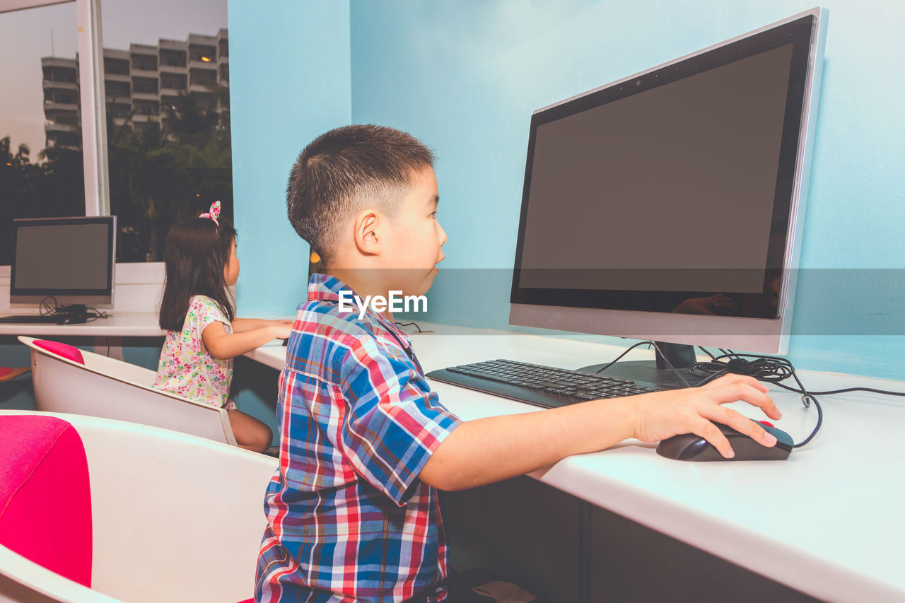 technology, child, childhood, real people, computer, males, men, connection, boys, table, one person, wireless technology, internet, casual clothing, lifestyles, indoors, computer equipment, computer network, innocence, surfing the net