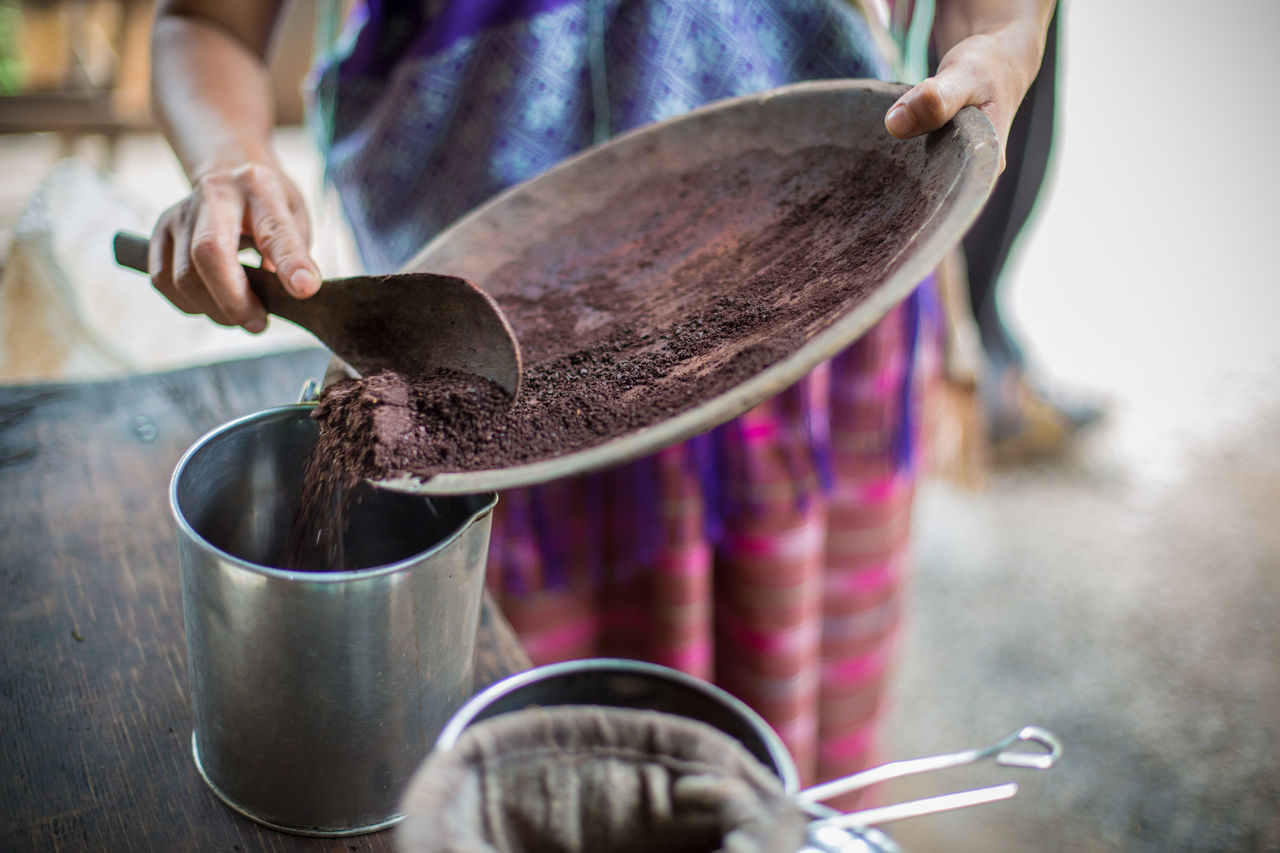 Close-Up Of Woman Roasting Coffee Beans