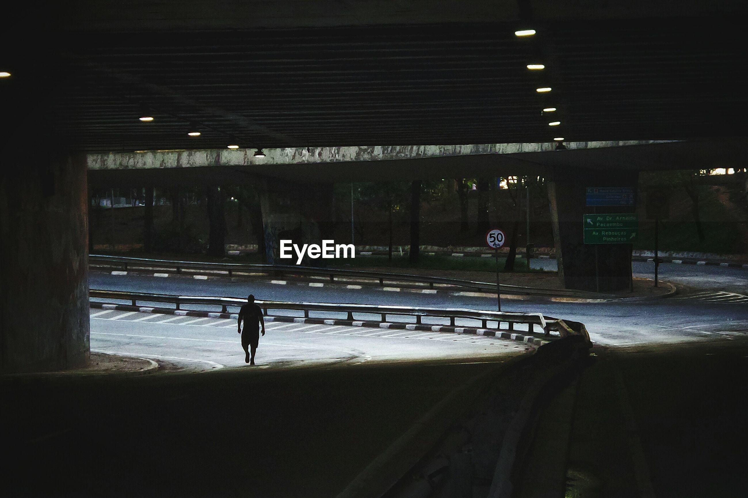 Man walking under elevated road
