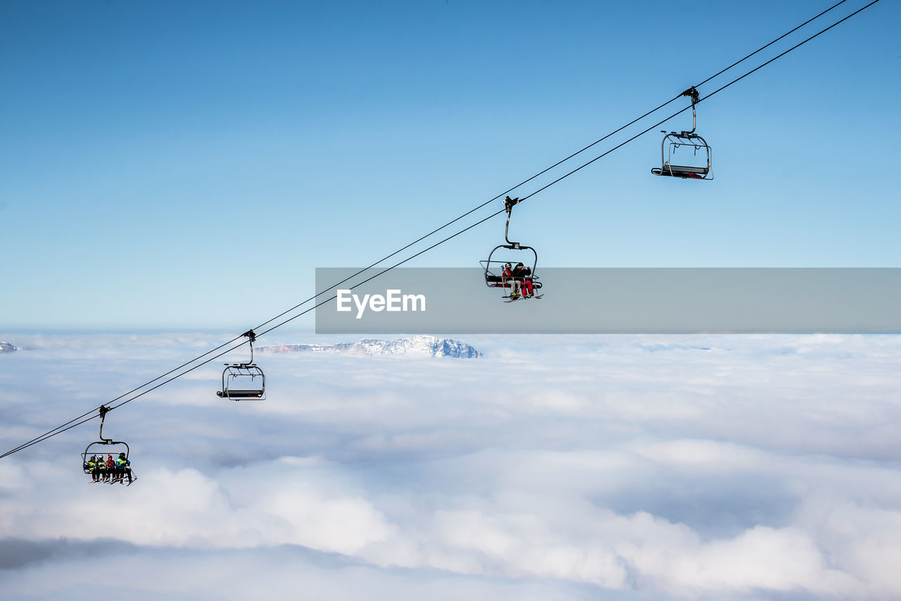 Ski Lifts Above Cloudscape Against Clear Sky